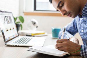 Man taking notes at a computer
